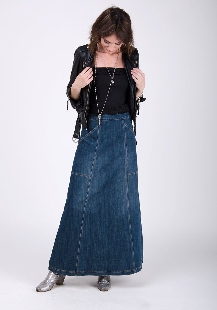 Full-front pose looking to floor wearing full flared shape of maxi skirt paired with leather biker jacket.