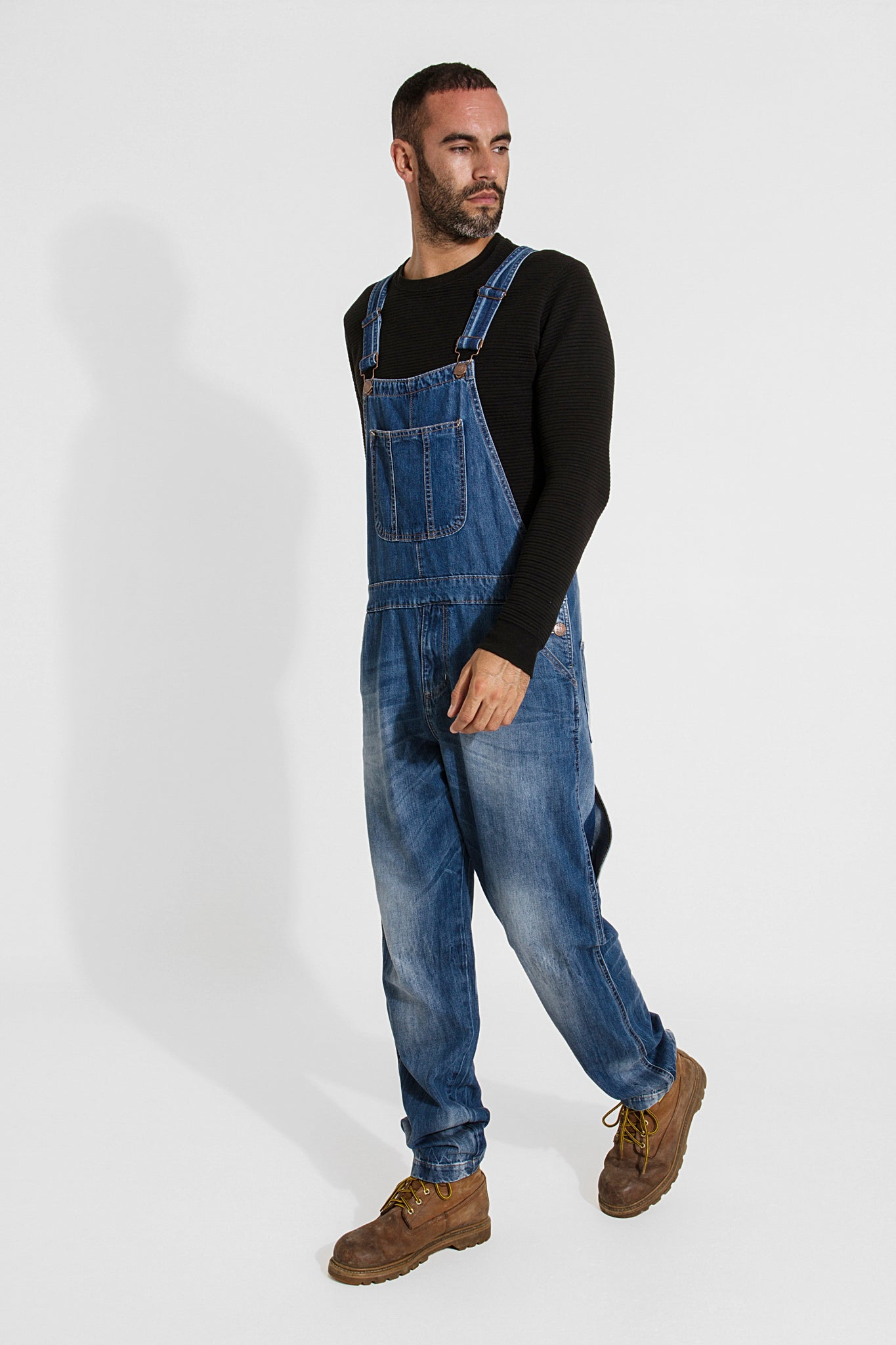 Full frontal-side pose looking to his left and walking, wearing bib-up midwash dungarees from Dungarees Online.