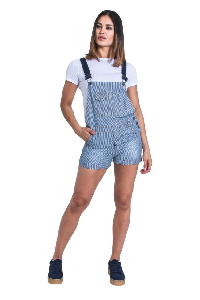 Full front view of model leaning on left hip with hand in right pocket, wearing women's 'Imogen' style, pinstripe denim dungaree shorts.