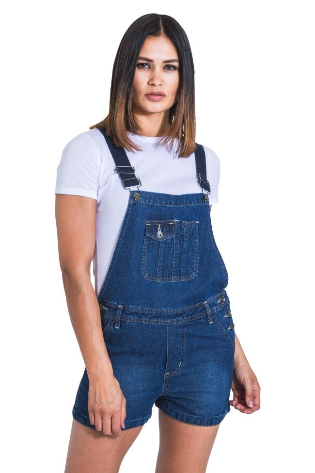 Two-thirds frontal view of model wearing 'Imogen' style denim dungaree shorts, with clear view of belt loops and turn-up detailing on hem.