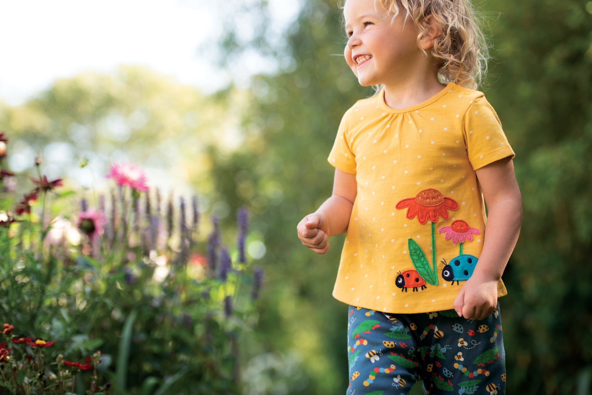 Girl toddler wearing a Frugi tshirt with ladybirds and floral trousers