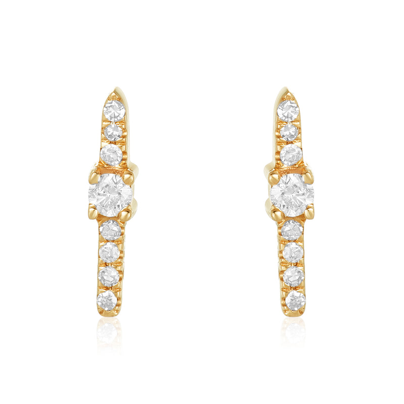 Dainty bar stud earrings in 14 karat gold with seven small diamonds and one larger diamond in the middle.
