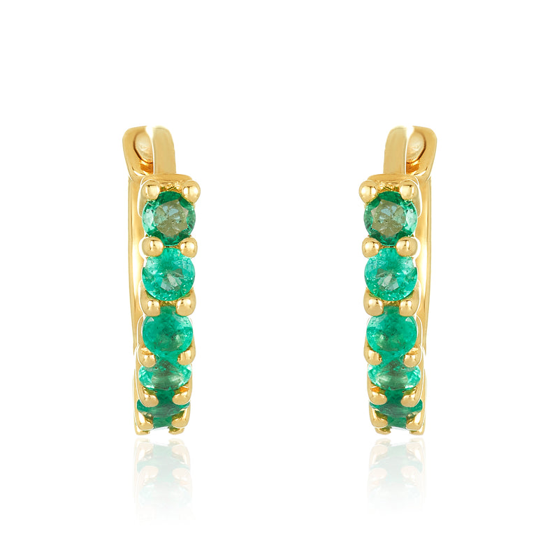 Huggie earrings in 14 karat yellow gold with emeralds on the front side.