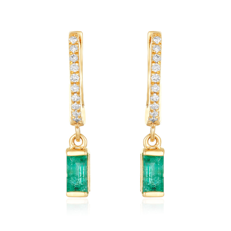 Dainty huggie earrings in 14 karat yellow gold with diamond pavé on the front with a delicate baguette-cut emerald charm.