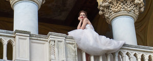 an-edmonton-bride-in-a-svitlana-custom-dress-sitting-on-the-railing-of-a-building