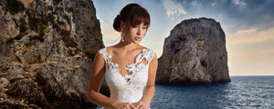 a-bride-in-a-svitlana-dress-standing-in-front-of-rocks-in-the-ocean