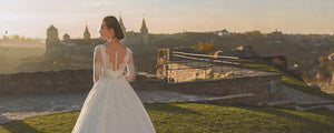 an-edmonton-bride-in-a-svitlana-custom-dress-standing-in-front-of-a-castle