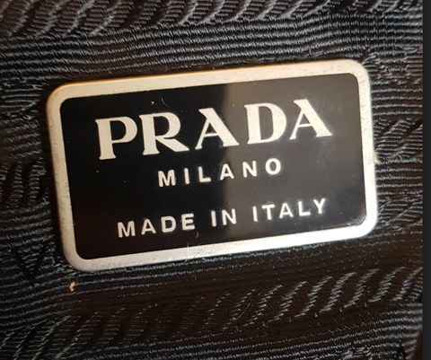 Black Prada square plate from the interior of the bags