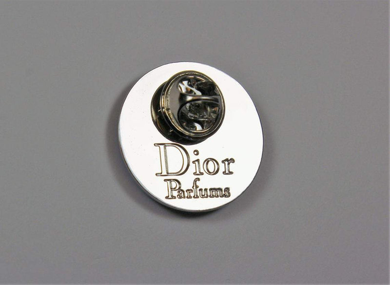 Christian Dior Dior Bee Pin with black background and white bee