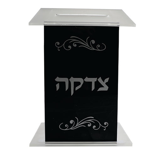 A SQUARE PERSPEX TZEDAKAH BOX 16X11X9 CM WITH SILVER PRINT- BLACK & CLEAR
