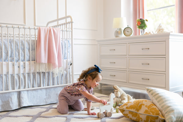 girl with dresser and crib