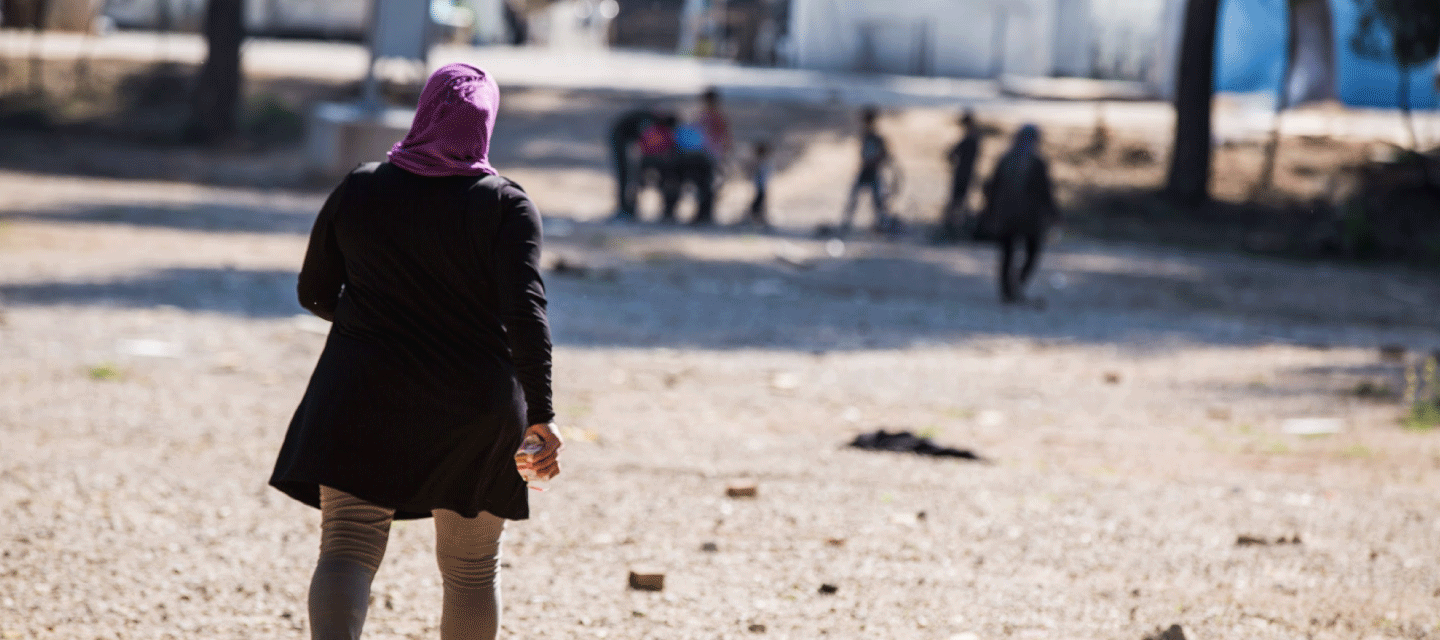 A woman walking in a refugee camp in Greece while children are playing.