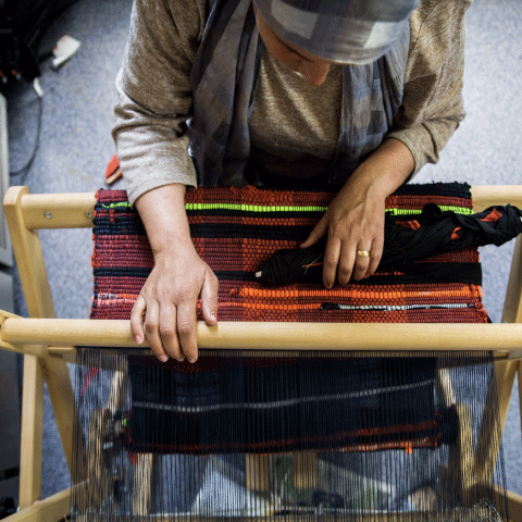A woman using the loom to create welcome mats in a refugee camp.