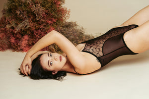 Model leaning back against a studio backdrop and dried flowers, wearing a black Kauf Bodysuit
