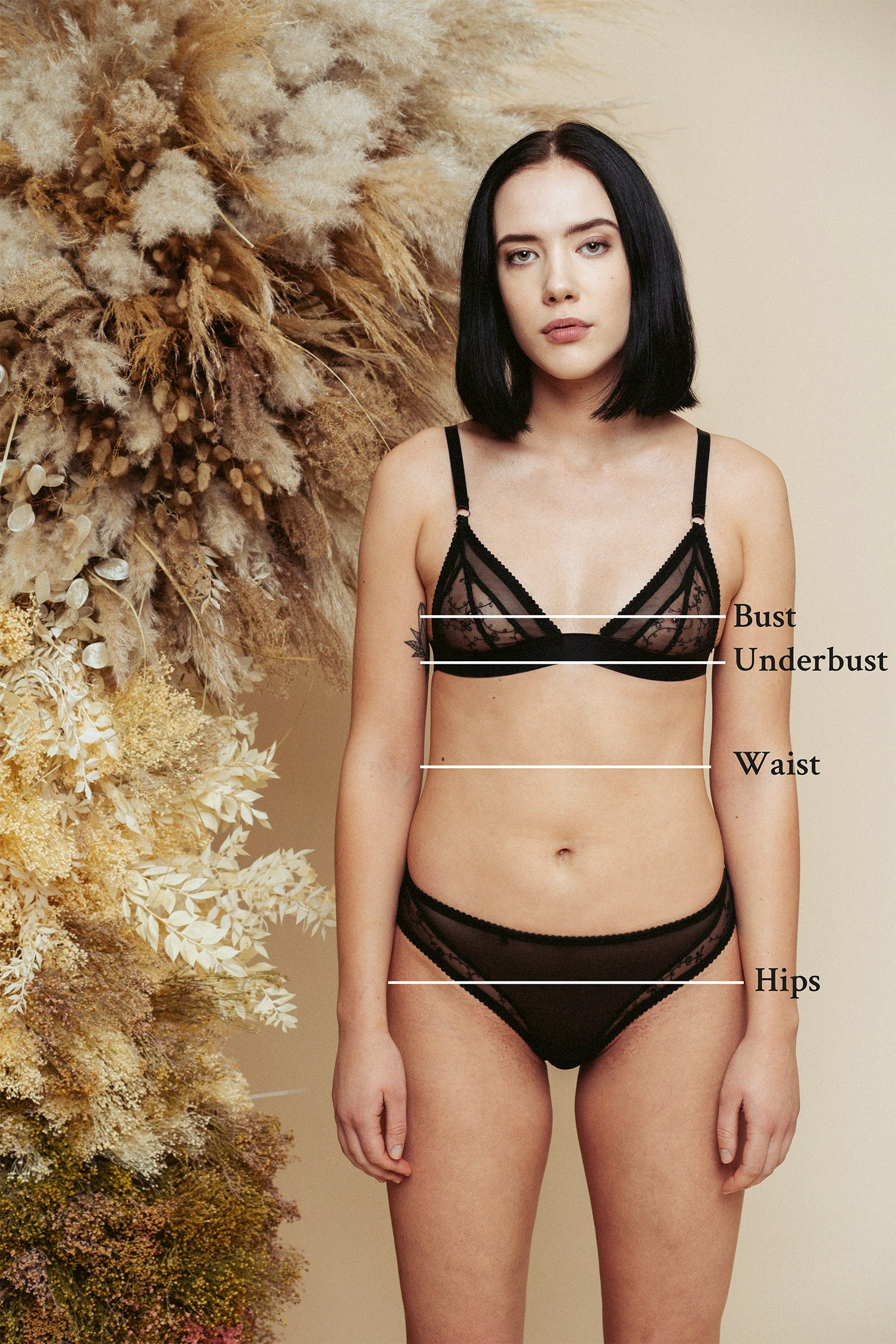 Kauf sizing reference image, model facing front and wearing black lingerie