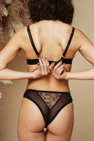 Model seen from the back, wearing the Kauf Brazilian Knicker and Triangle Bralette in black