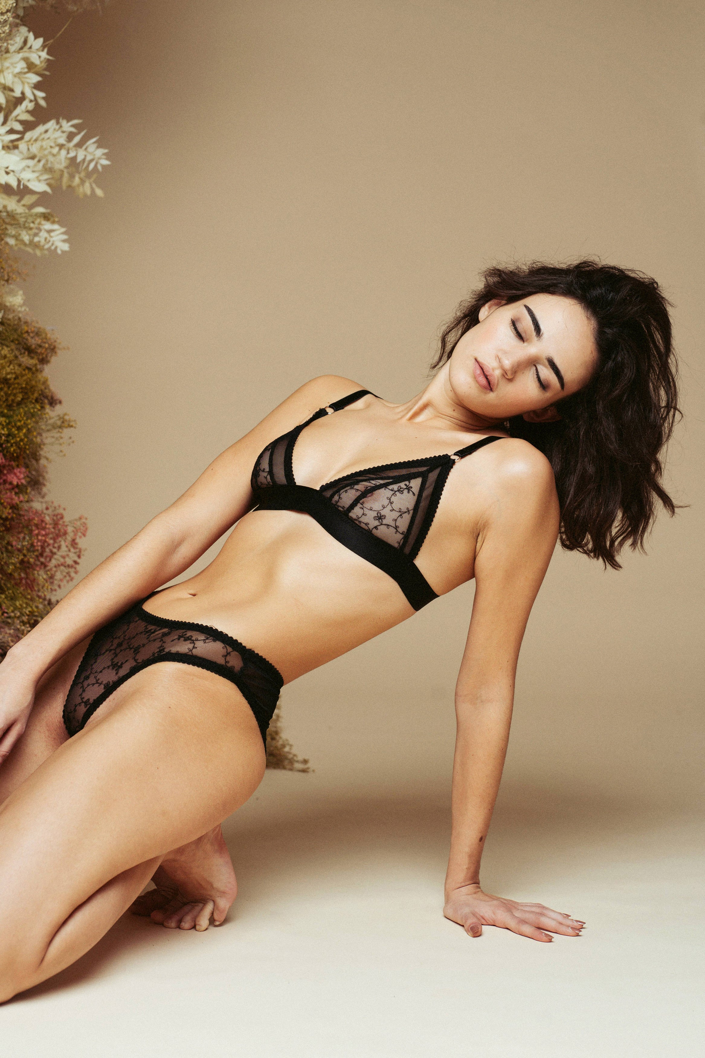 Model kneeling on the floor and leaning back, wearing the Kauf Triangle Bralette and Brazilian Knicker in black