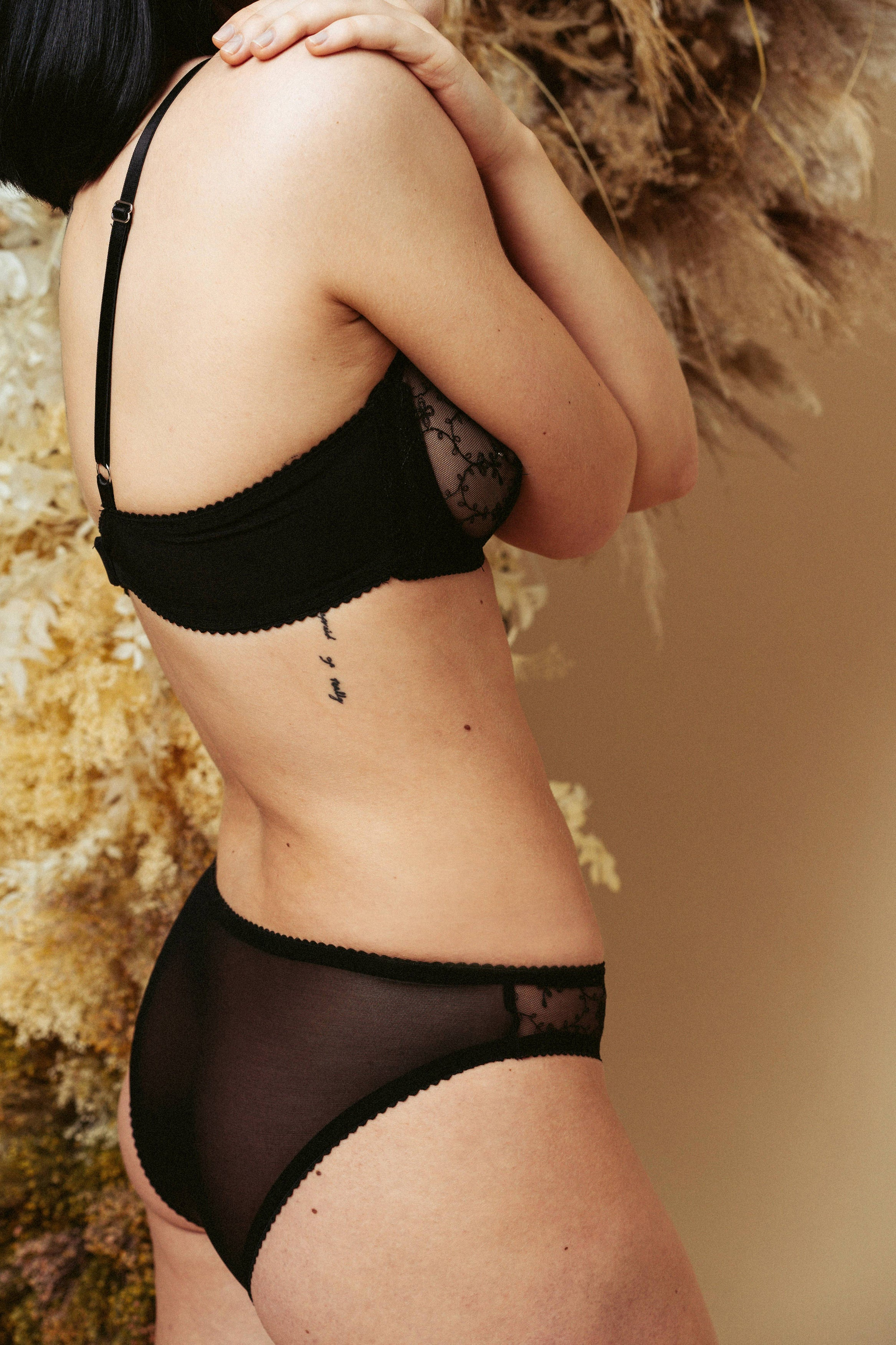 Model seen from the side and wearing the Kauf High Leg Knicker and Bandeaux Wire Bra in black