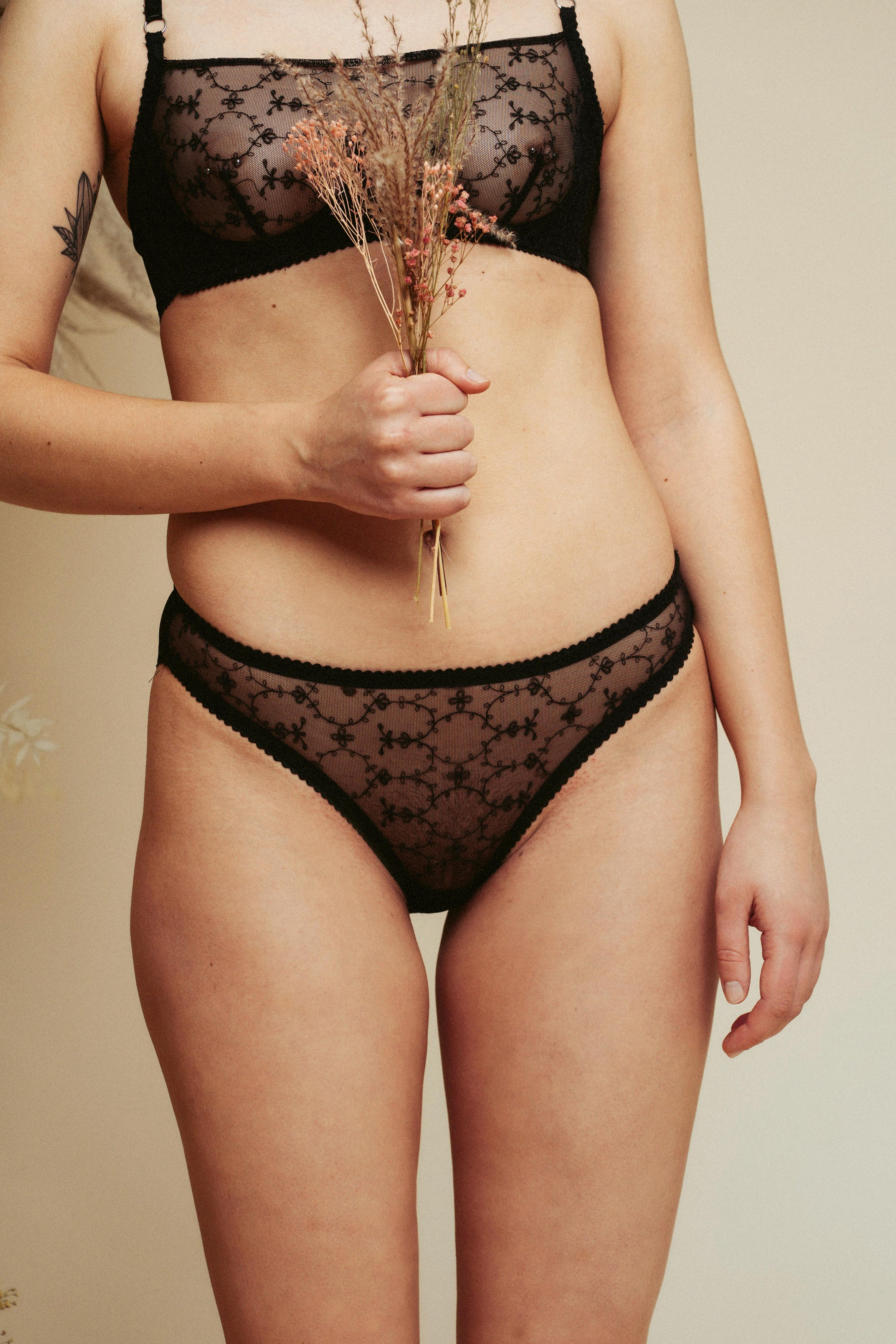 Model holding some dried flowers and wearing the Kauf High Leg Knicker and Bandeaux Wire Bra in black