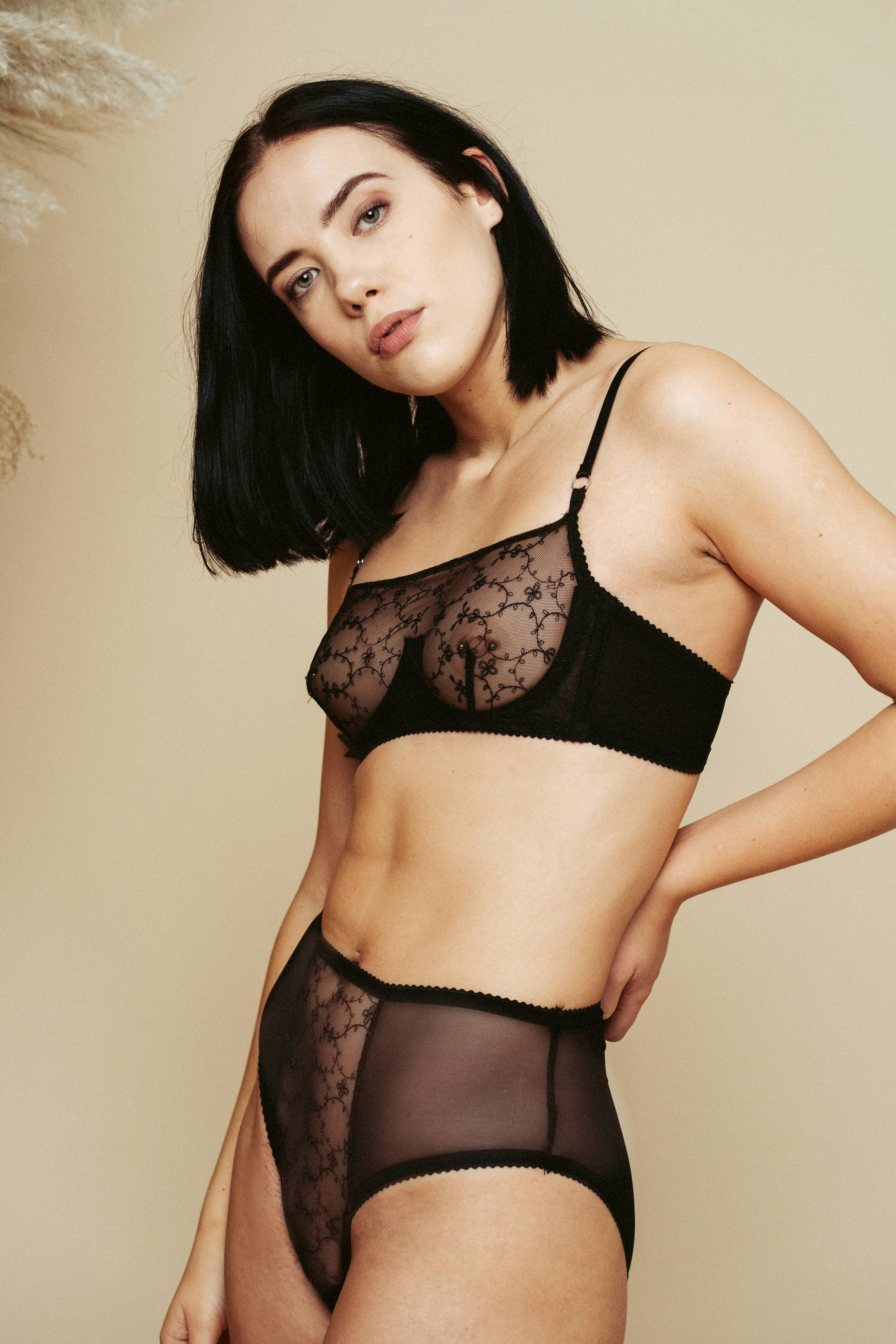 Model wearing the Kauf High Waisted Knicker and Bandeaux Wire Bra in black, with her hand on her hip