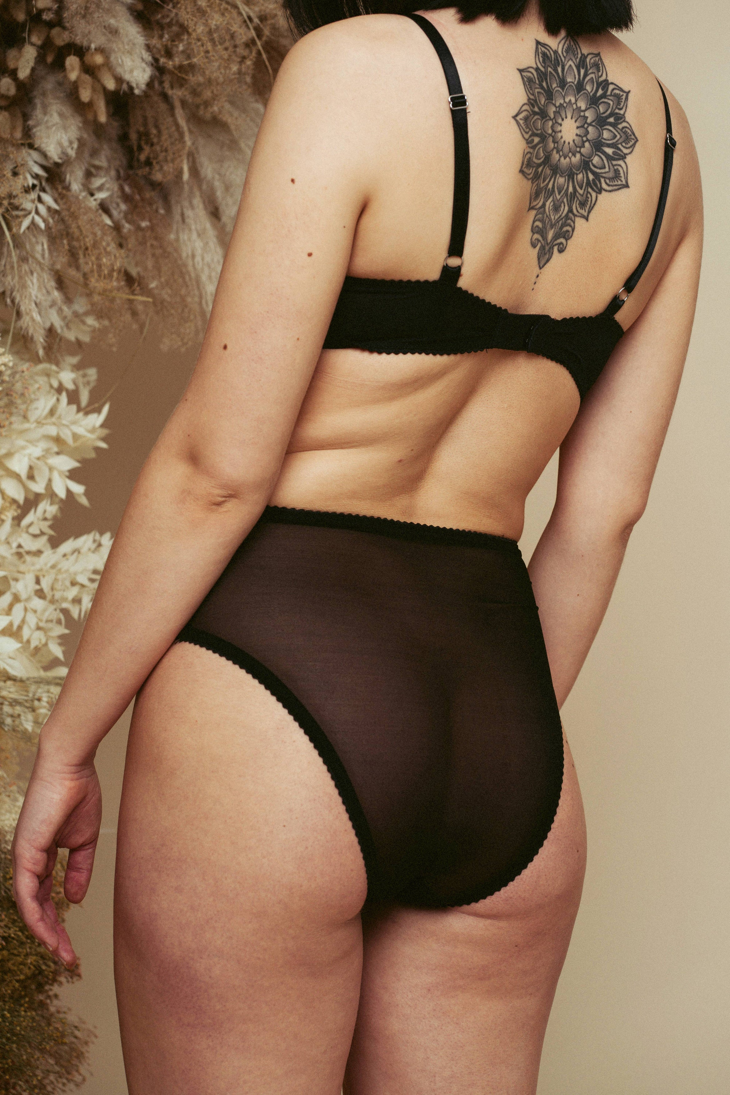 Close up of model seen from the back, wearing the Kauf High Waisted Knicker and Bandeaux Wire Bra in black