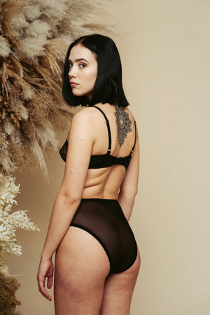Model seen from the back, wearing the Kauf High Waisted Knicker and Bandeaux Wire Bra in black