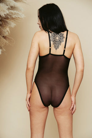 Model shot from the back, wearing the Kauf Bodysuit in black with lace panels