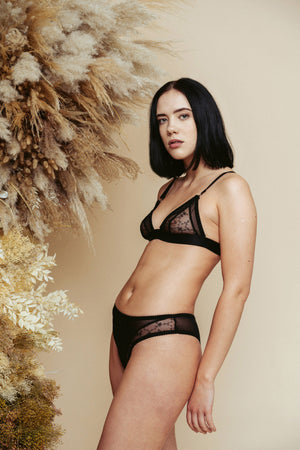 Model seen from the side, wearing the Kauf Triangle Bralette and Brazilian Knicker in black