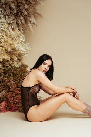 Model sitting on the floor, wearing the Kauf Bodysuit in black with lace panels
