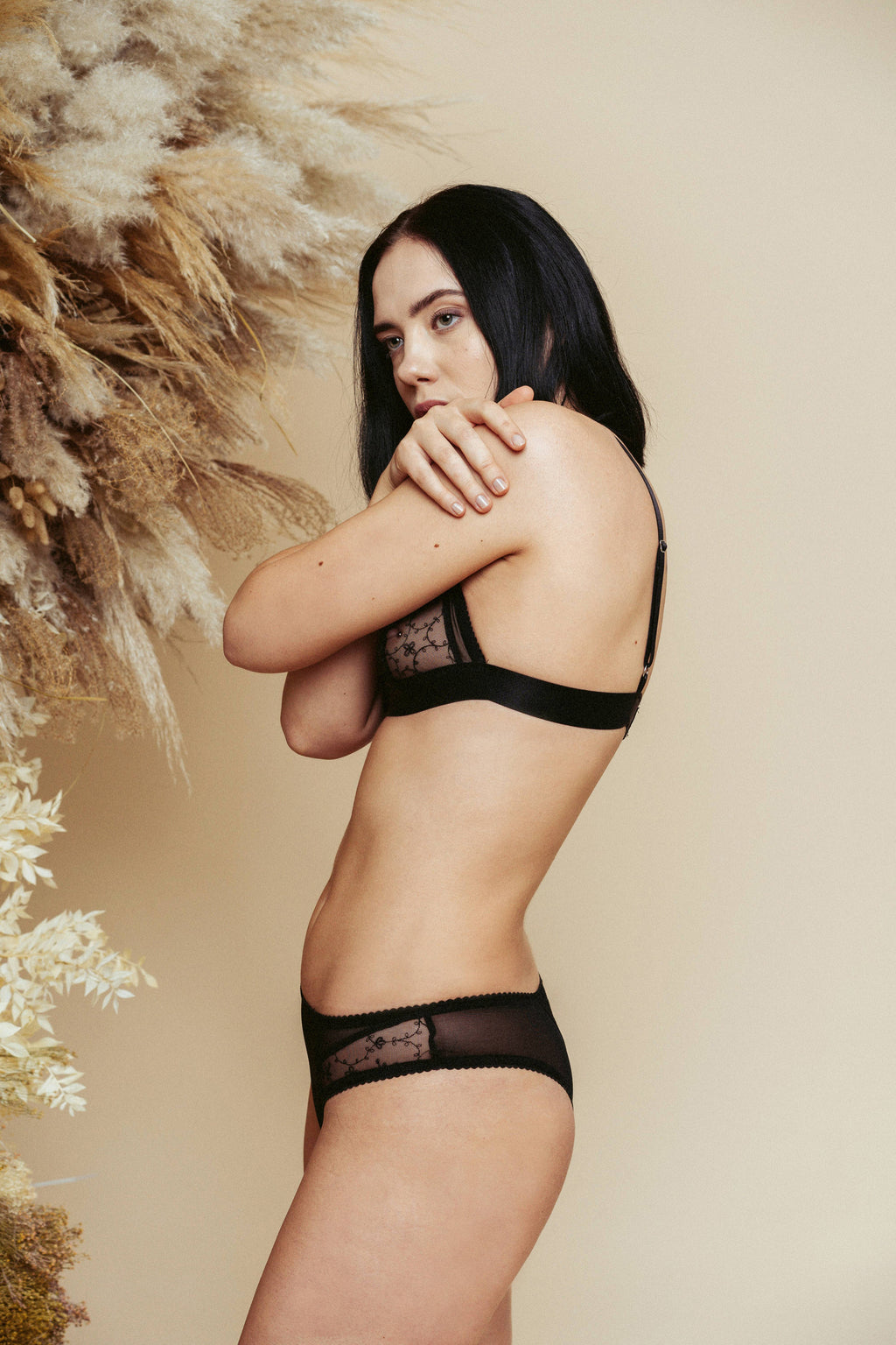 Model shot from the side, wearing the Kauf Brazilian Knicker and Triangle Bralette in black