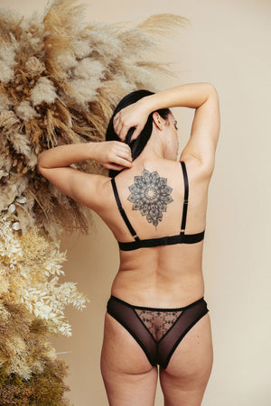 Model seen from the back, wearing the Kauf Triangle Bralette and Brazilian Knicker in black