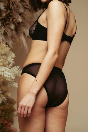 Model seen from the back and wearing the Kauf High Leg Knicker and Bandeaux Wire Bra in black