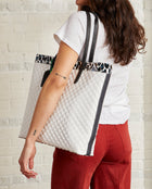 Tate Slim Tote with quilted white exterior and Lola ConsuelaCloth accent by Consuela, model view