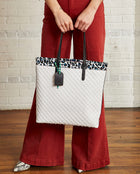 Tate Slim Tote with quilted white exterior and Lola ConsuelaCloth accent by Consuela, lifestyle view
