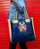 Felicia Classic Tote with quilted blue exterior and embroidery by Consuela, model view