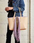 Kai Breezy East/West Tote in natural untreated leather with purple trim and beads by Consuela, model view