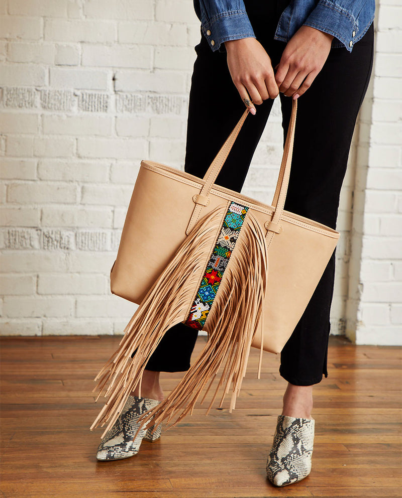 Shakira Breezy East/West Tote in natural untreated leather with fringe and beading detail by Consuela, model view