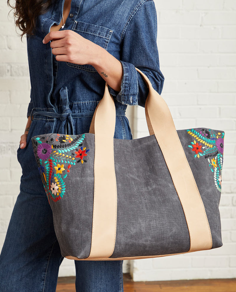 Alexis Large Carryall in grey waxed canvas exterior with colorful floral embroidered accents by Consuela, model view