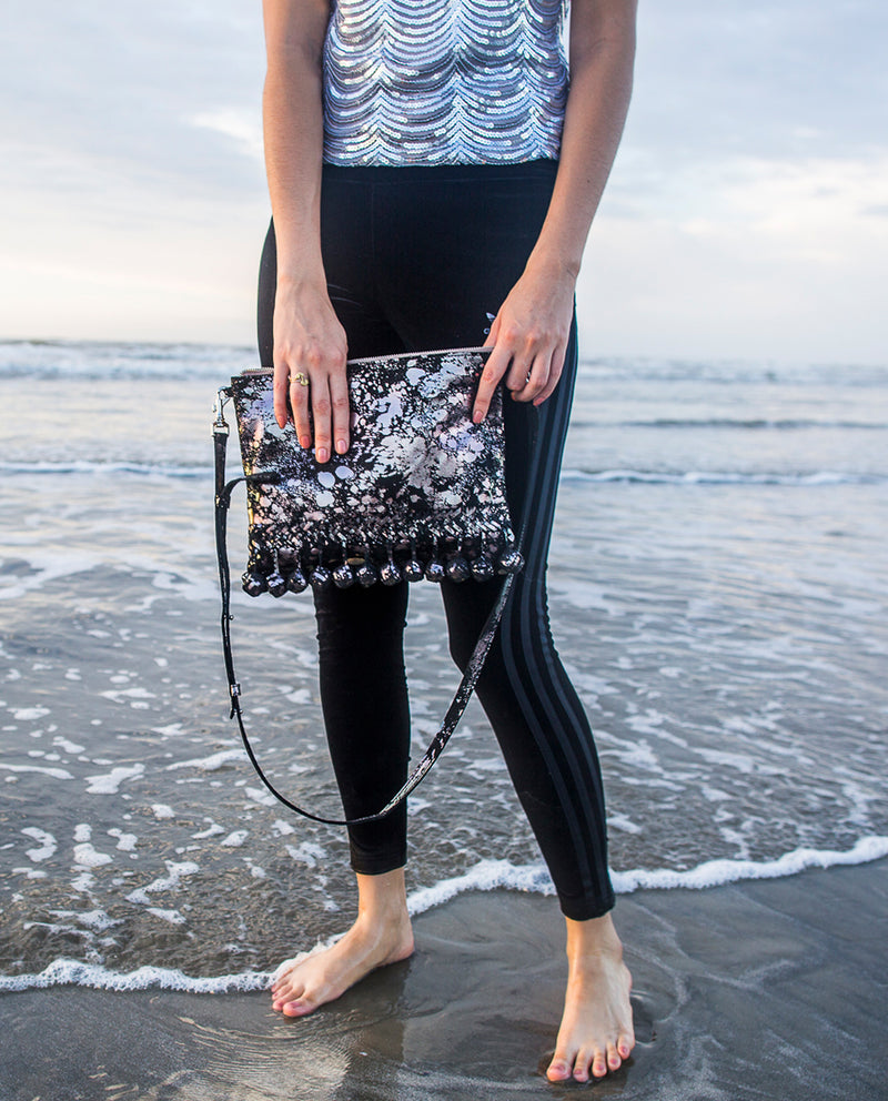Charli Fiesta Crossbody in black metallic leather by Consuela, lifestyle holding on a beach