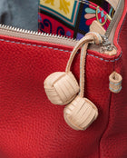 Valentina Fiesta Crossbody in red pebbled leather by Consuela, hand tied ball fringe pull