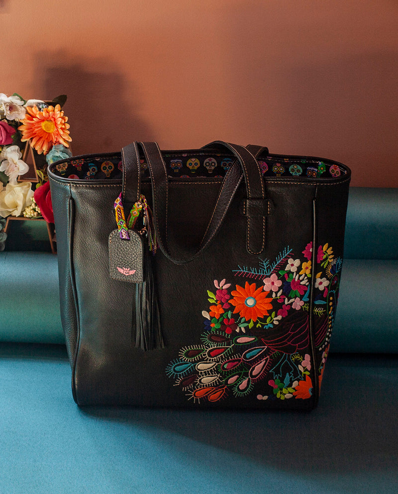 Shady Classic Tote in black leather with peacock embroidery by Consuela, lifestyle image on blue floor