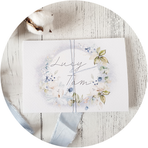 Dusty blue and floral wreath A6 Poppleberry all-in-one wedding invitation on white cardstock wrapped in dusty blue silk thread