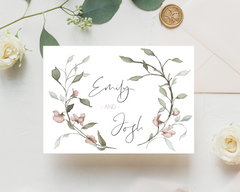 Watercolour Pink Flowers A6 Poppleberry accordion fold all-in-one wedding invitation, folded on eucalyptus leaves.