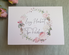 Close-up of a blush floral wreath A6 Poppleberry accordion fold all-in-one wedding invitation, folded into its A6 size.