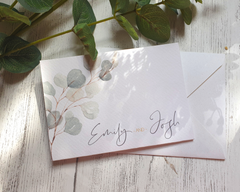 Close-up of a green eucalyptus A6 Poppleberry accordion fold all-in-one wedding invitation, folded on an ivory envelope