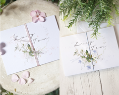 Watercolour blush pink or blue A6 Poppleberry accordion fold all-in-one wedding invitation, folded & tied in matching twine.