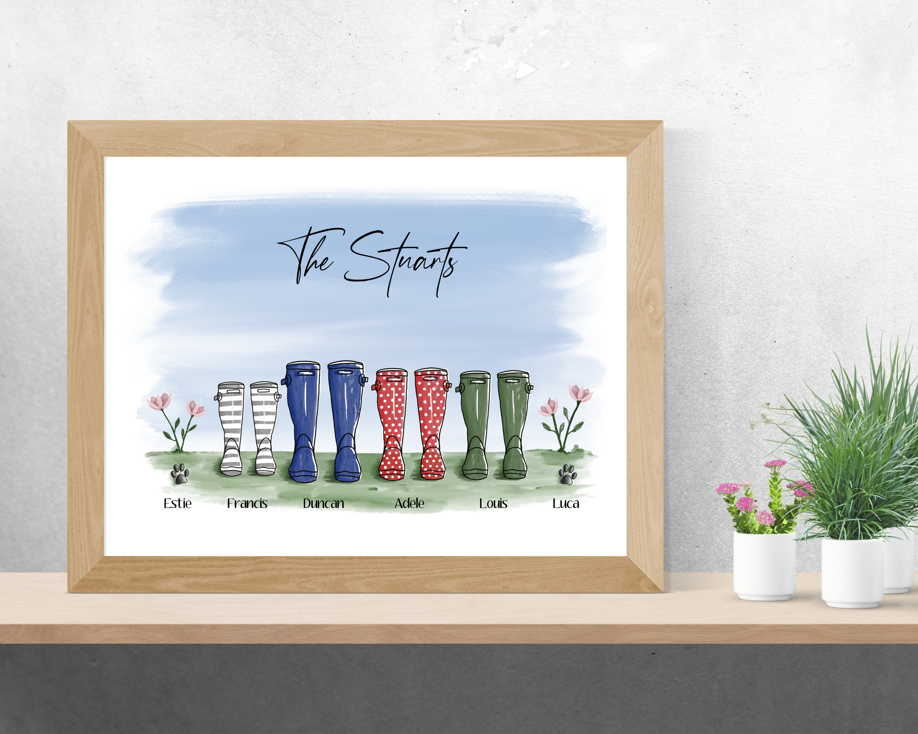 Poppleberry family of colourful wellington boots digital drawing art print, in a wooden frame on wall.