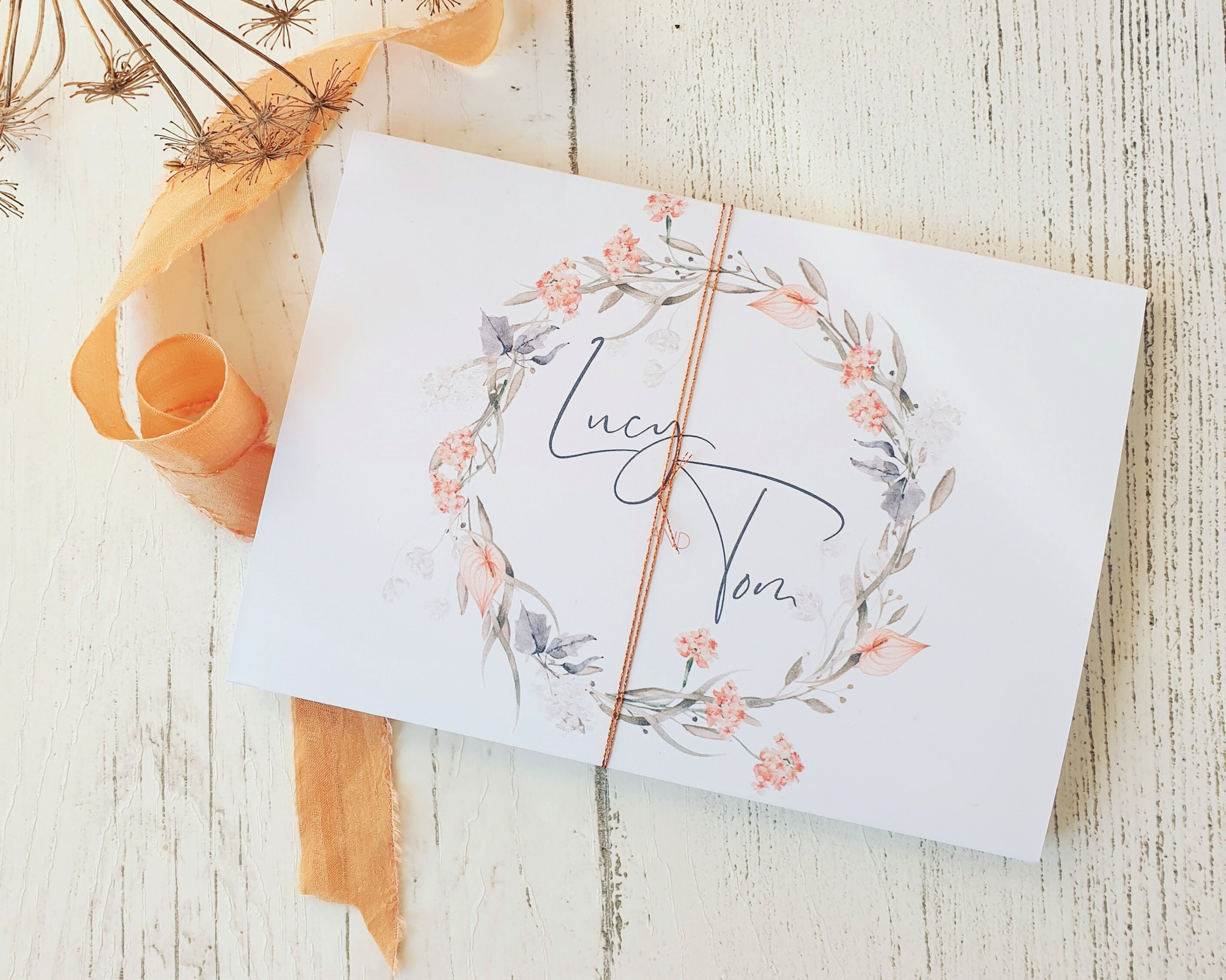 Coral pink wreath A6 Poppleberry accordion fold all-in-one wedding invitation, folded with matching coral silk tread wrap.