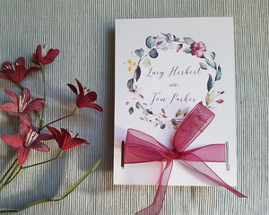 Front of a burgundy floral A6 Poppleberry mini pocket-fold wedding invitation set, with matching burgundy organza bow.