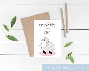 Poppleberry A6 folded birthday card, with a smiling white sheep illustration, on white cardstock and kraft brown envelope.